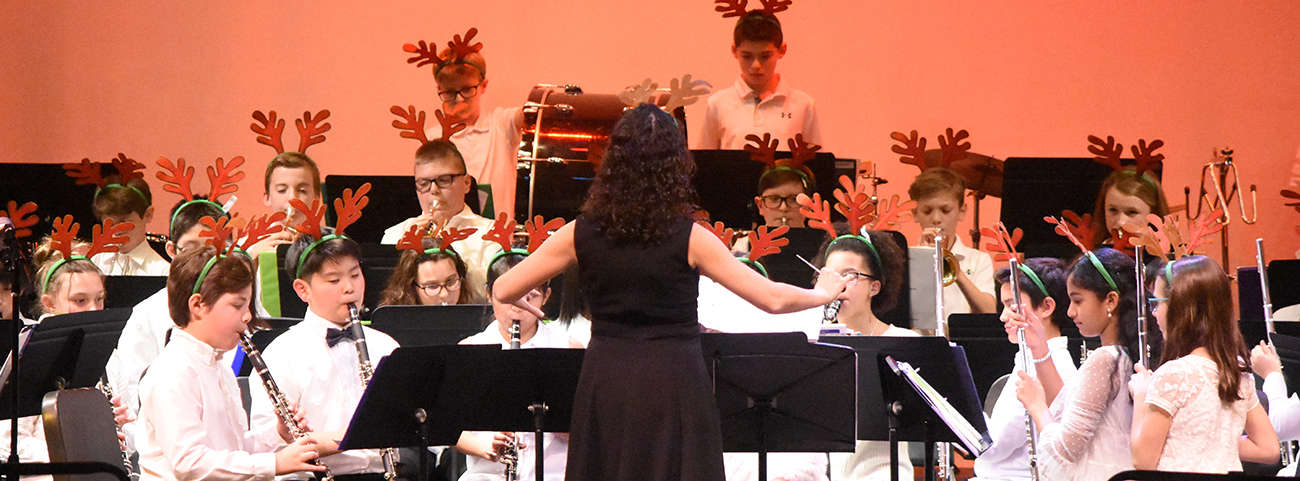 Conductor stands in front of band students wearing reindeer antlers