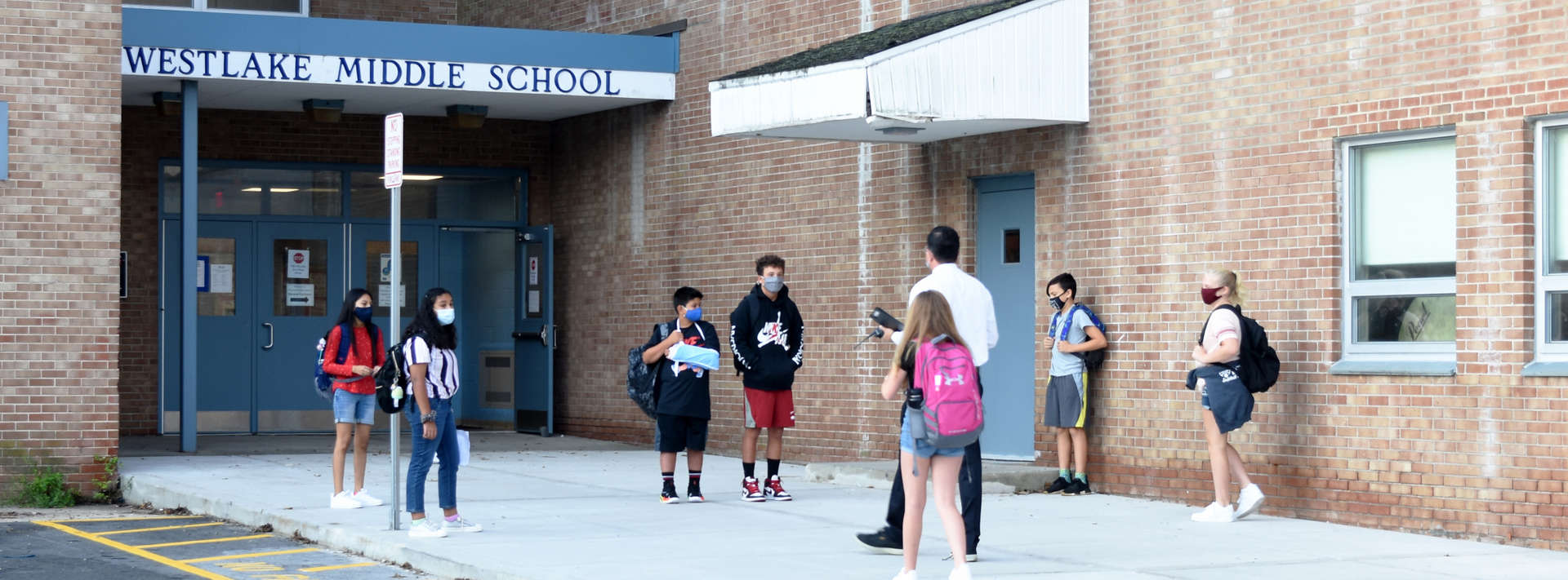 group of kids walks towards school entrance with adult