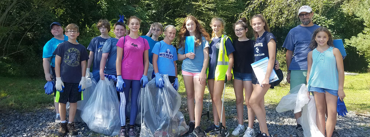 Group of students clean garbage from reservoir area.