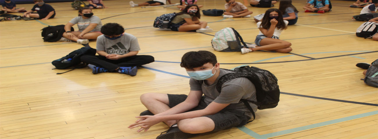 Students who arrived early wait for school to start in the gym wearing masks and practicing social distancing.