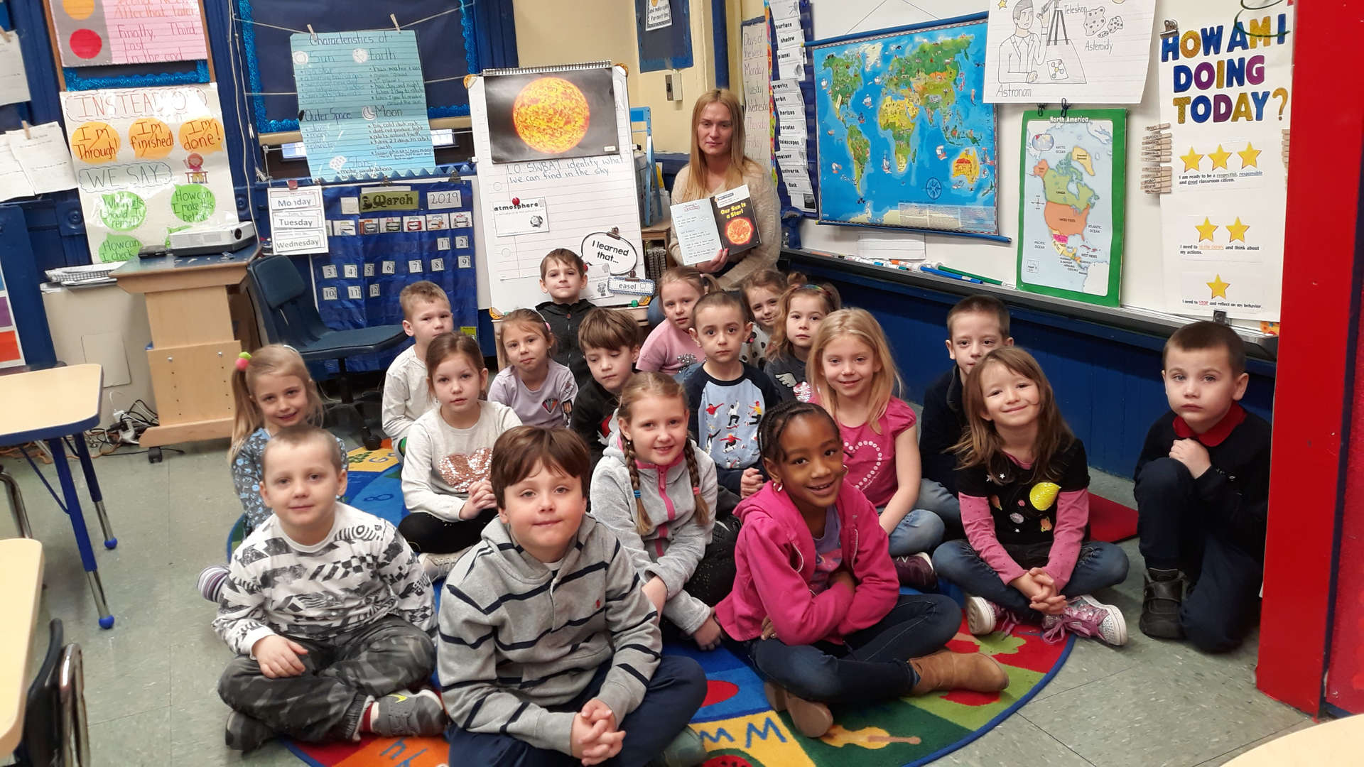1st grade dual language class sit for a story with their teacher