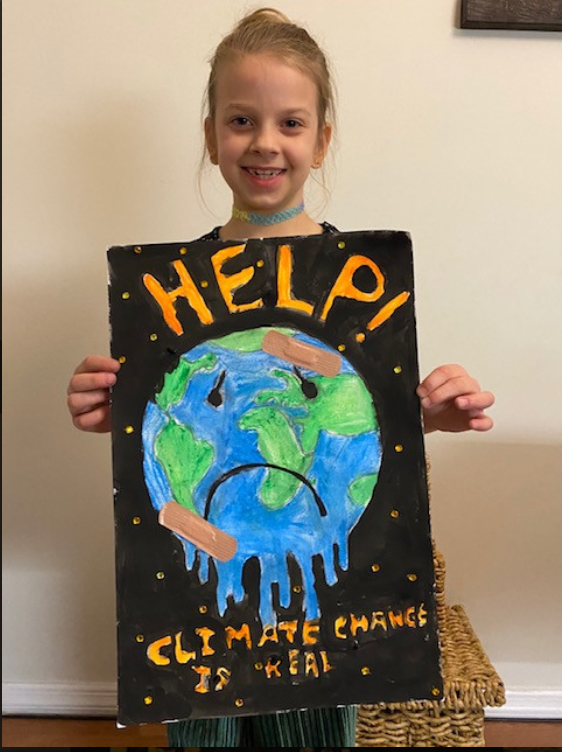 Girl holding poster with a drawing of the earth melting saying is Climate Change is real