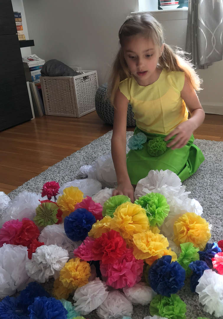 Fashion show student working making plastic bag flowers.