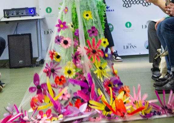 Fashion show participant on the runway wearing a long plastic dress with plastic colorful flowers