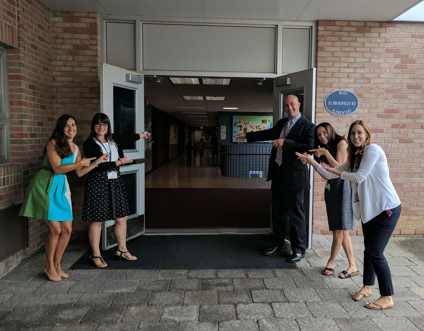 Administrator and teachers welcoming visitors