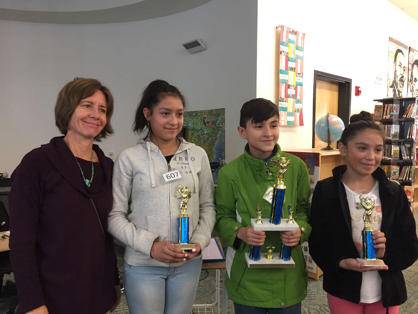3 students and teacher with trophies