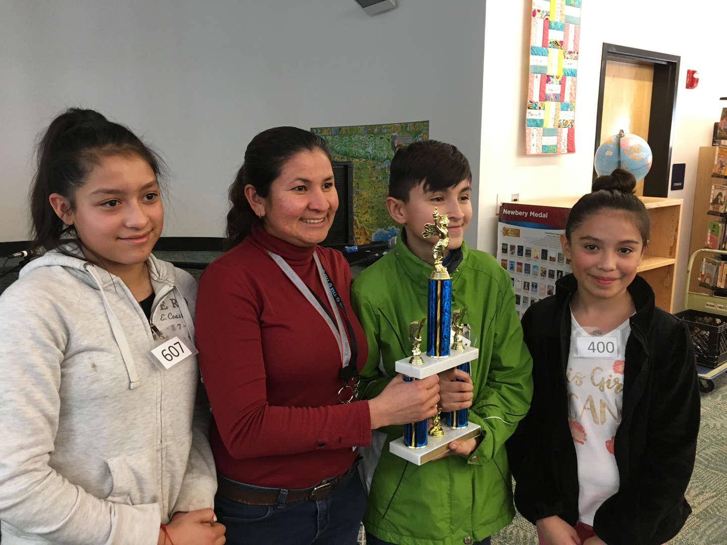 3 students and teacher with trophy