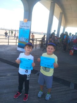 Two students holding participation certificates at the beach clean up