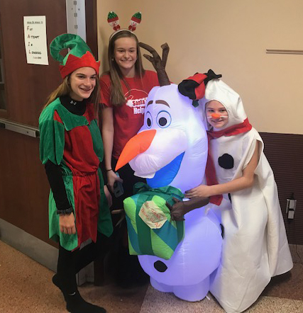 Students in dressed as an elf, a reindeer and a snowman posing with an inflatable Olof from Frozen.