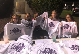 "Students selling ""Cougars for a Cure"" t-shirts at the football game."