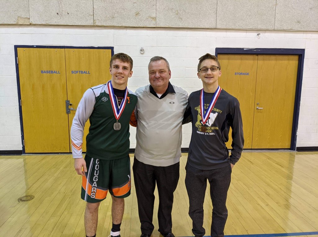 Wrestlers Glenn Christner and Shane Momyer are shown at sectionals with Athletic Director Tom Evans.