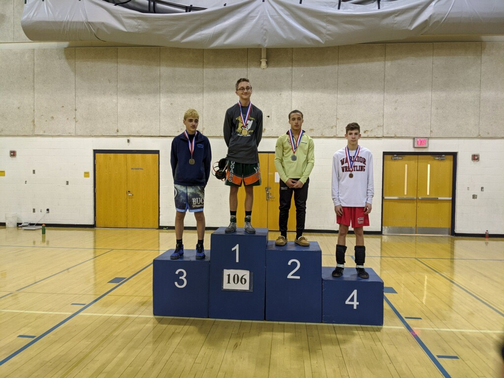 Wrestler Shane Momyer on the podium at sectionals FIRST PLACE (106 weight class)