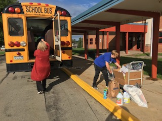 Mrs. Huss and Miss Dahlstrom stuffing a bus for flood victims.