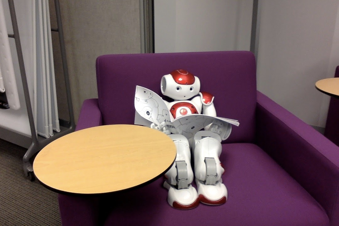 Nao Robot reading on a chair