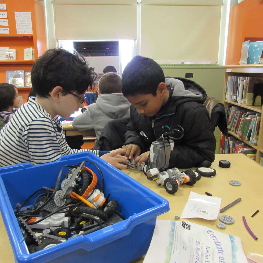 students assembling lego robotics in the school library