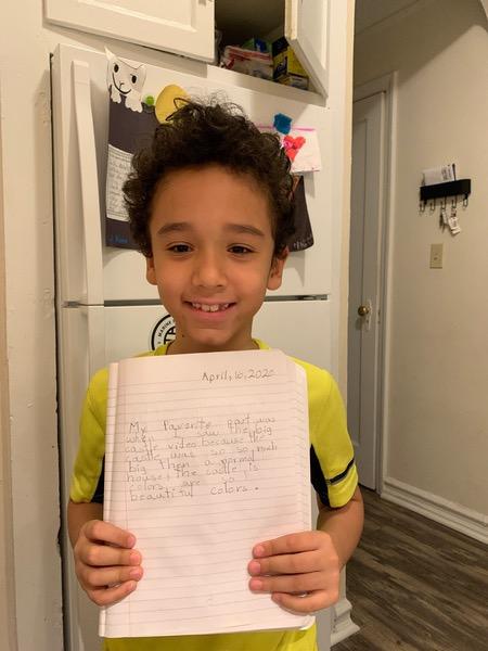 boy in yellow shirt shows his writing