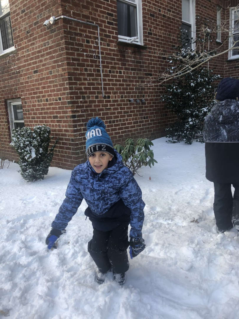 boy sitting in the snow with blue jacket
