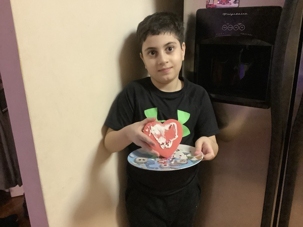 boy holding his decorated heart cookie
