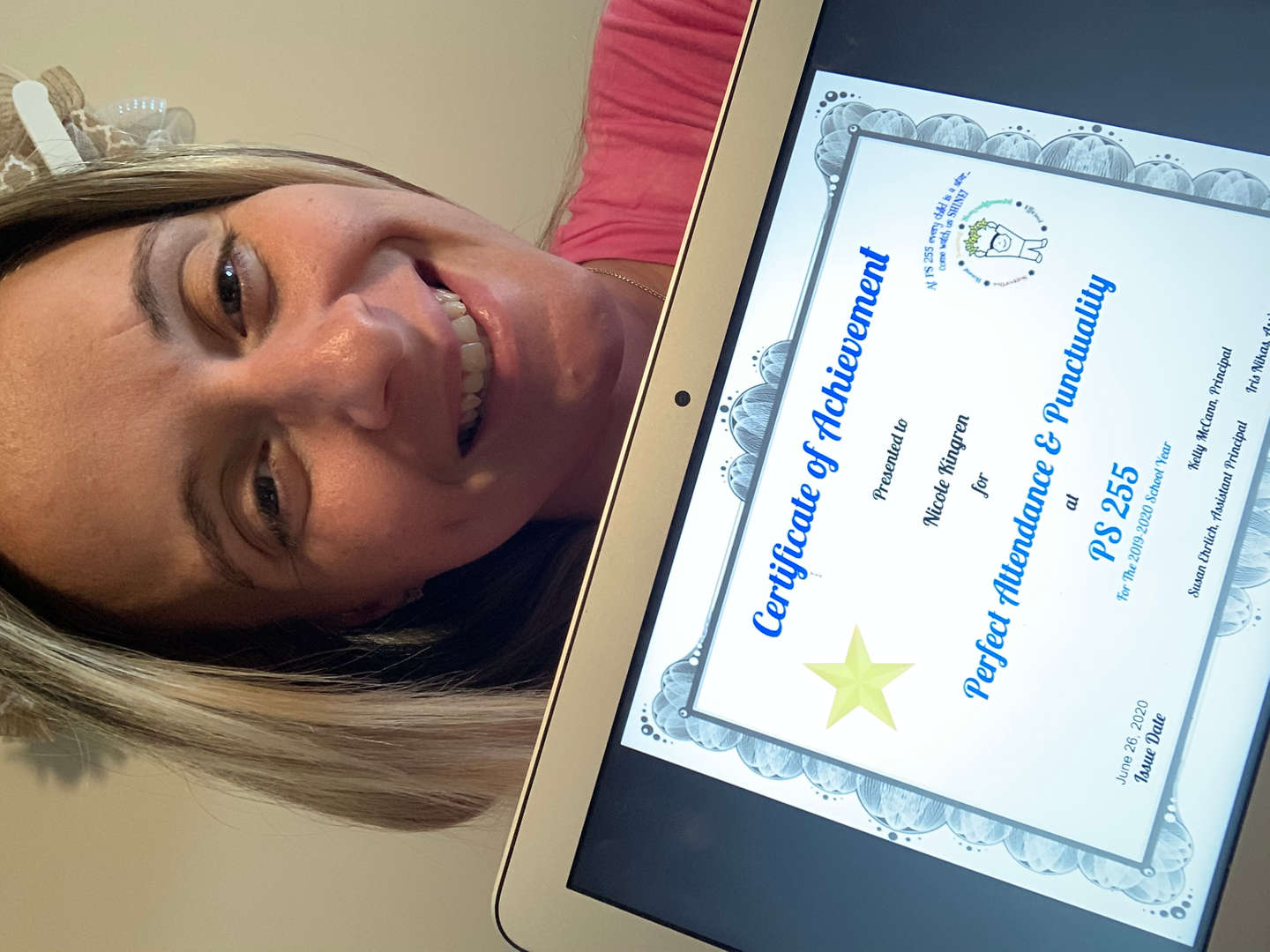 Mrs. Kingren holds her certificate for a picture