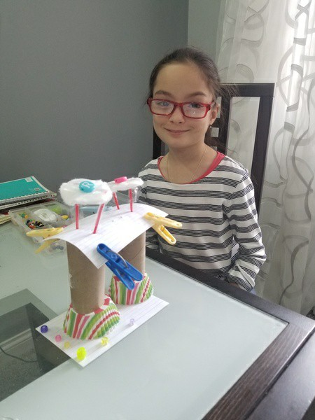 girl stands behind her creation