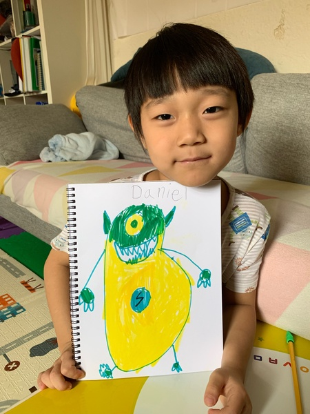 girl holds her yellow and green monster