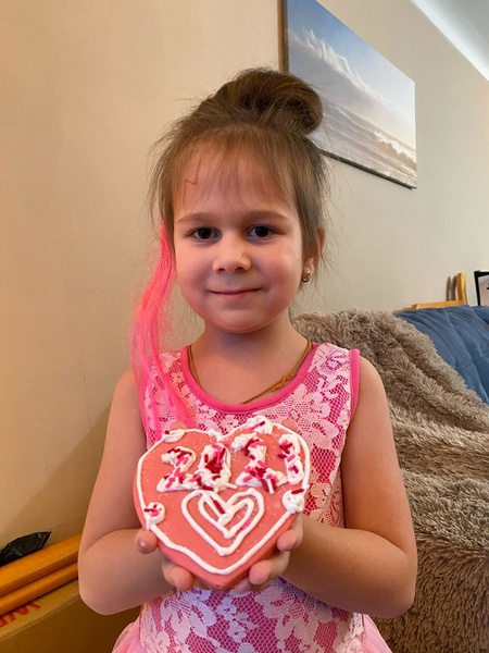 student in pink holds her pink decorated heart cookie