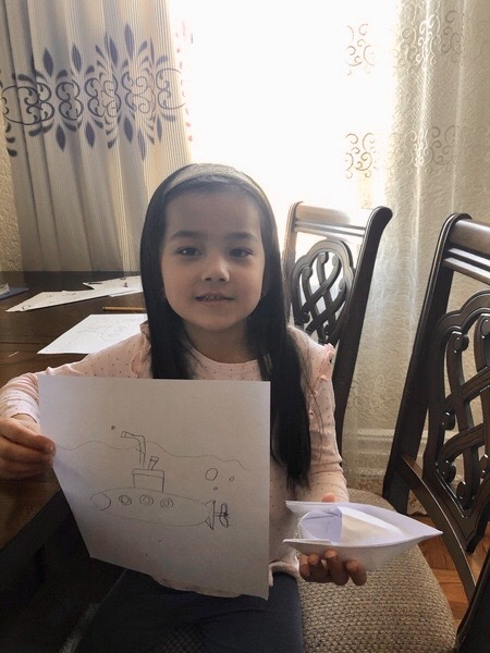 girl sits at the dining room table sharing her work