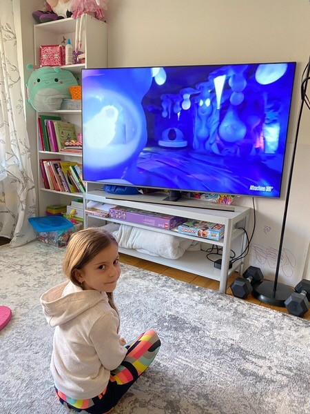 girl watches the tv from the floor