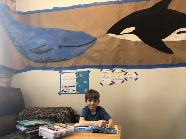 the child sits below his whale artwork