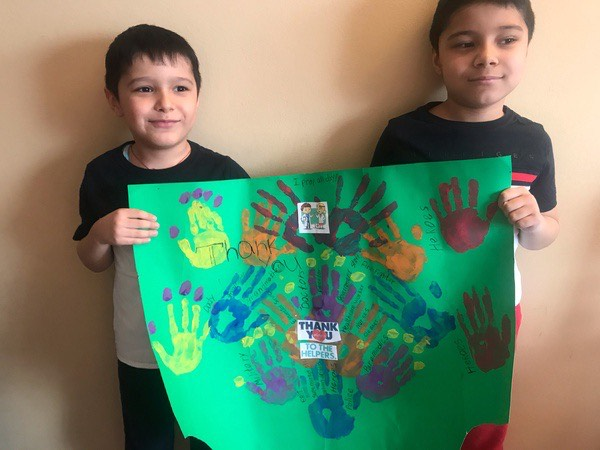 brothers hold a green poster