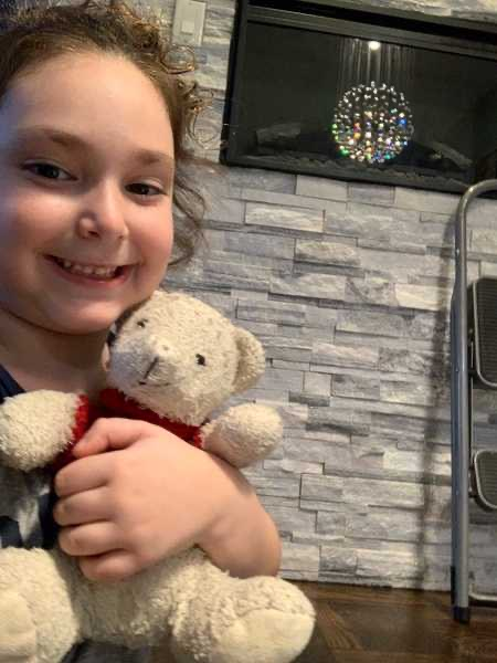 smiling child with stuffed animal