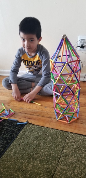 the child sits next to his colorful creation
