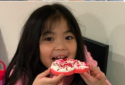 girl in a pink shirt takes a bite of her cookie