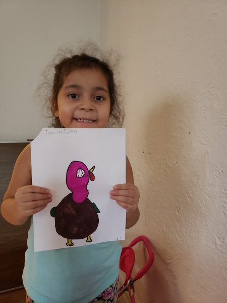 Girl holding turkey with red head and brown body