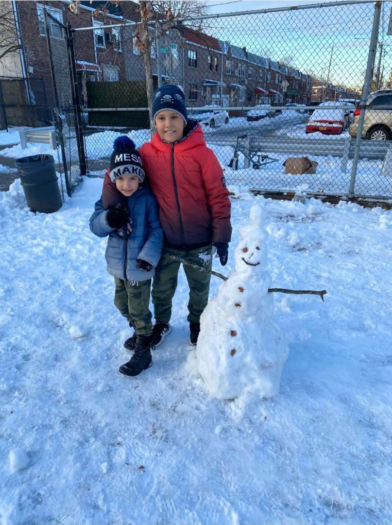 siblings standing next to a tiny snowman