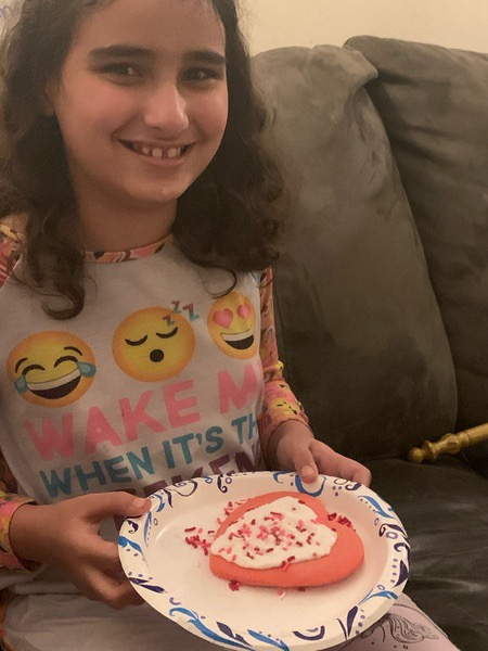 child with emoji shirt and decorated heart cookies