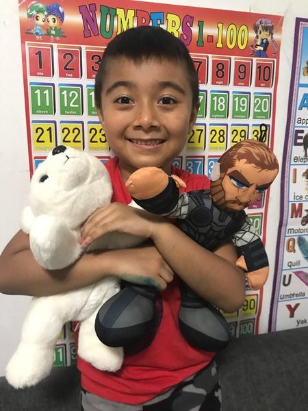 child standing holding super hero and stuffed bear