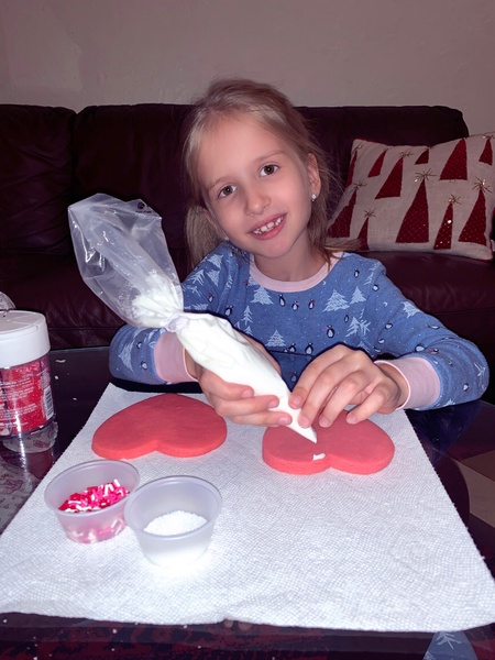 girl using icing to decorate her cookie