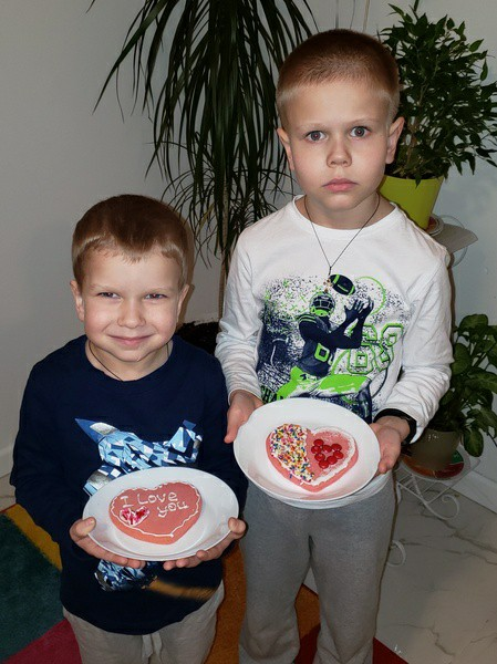 siblings show their decorated cookies on a white plate