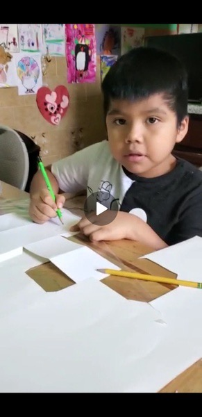 boy uses his green pencil to complete his work