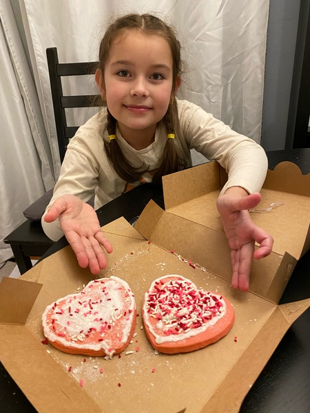 girl showing us her two decorated cookies