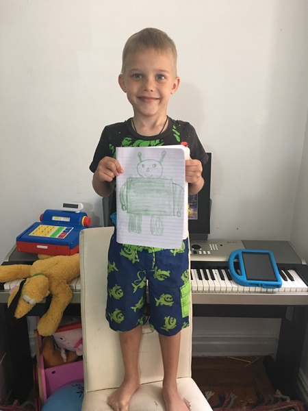child standing holding drawing with technology in the background