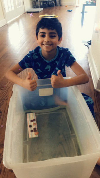 child gives thumbs up for his penny boat