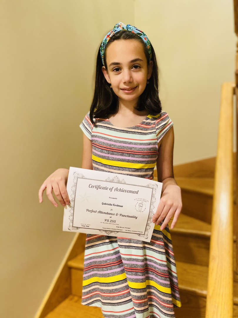 girl holds her certificate next to wooden table