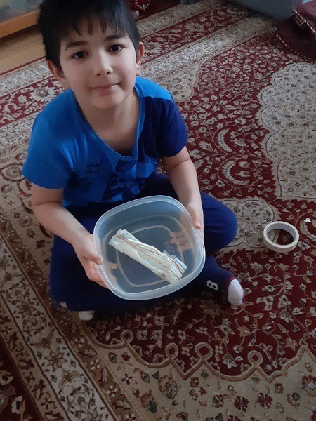 the child holds the Tupperware with his penny boat