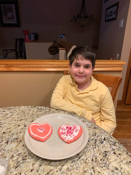 child posing with her decorated cookies