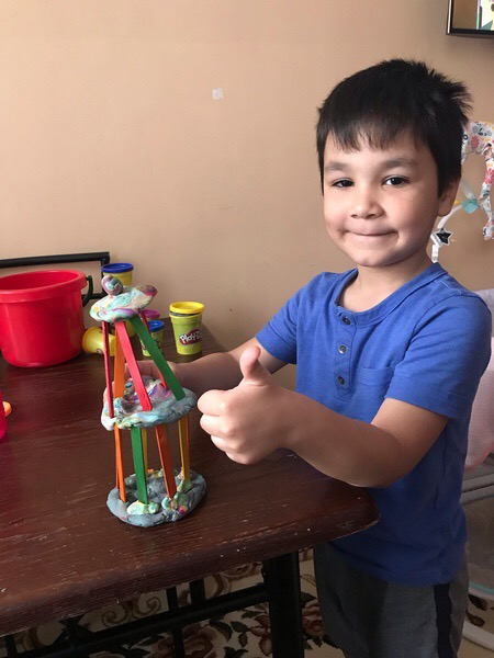 the child gives a thumbs up next to his colorful creation