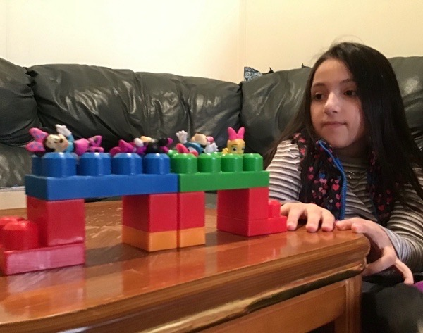 child made a bridge out of large legos