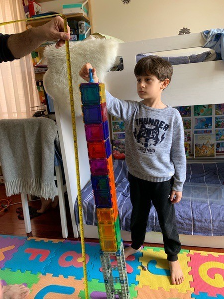 the boy gently places a block on the tall structure