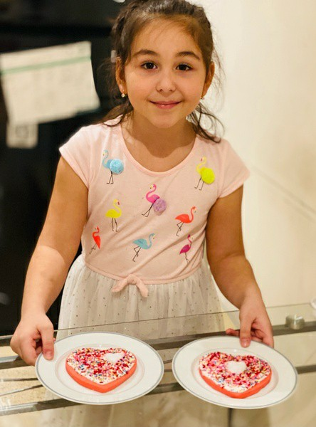 smiling girl shows her decorated heart cookies
